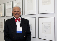 Photograph, Warren Washington in front of the American Academy of Arts and Sciences wall of acceptance letters