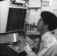 Photograph, Warren Washington using microfilm reader